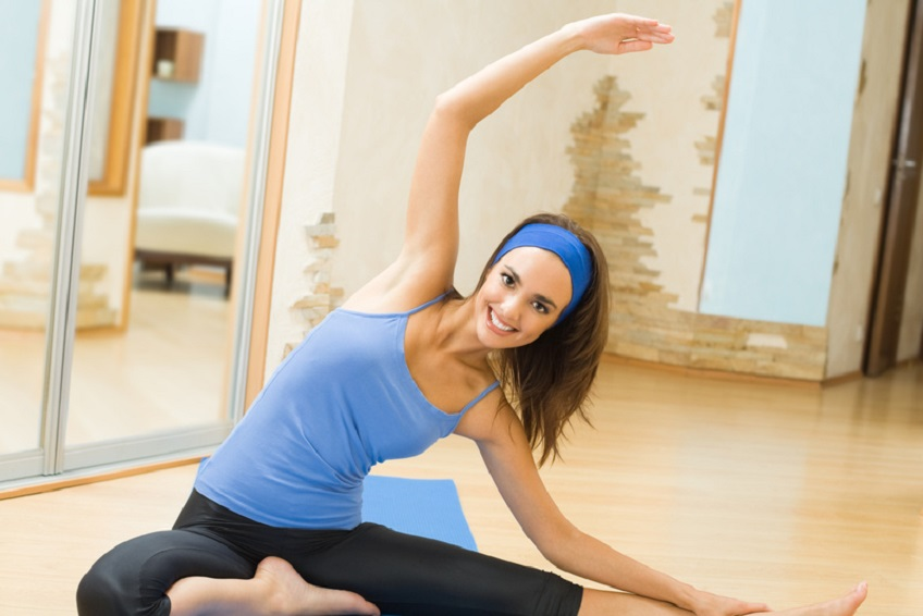 Young happy woman exercising at home